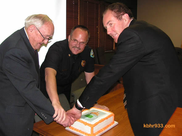 The Firewise honor was then celebrated with a cake, which Chief Willis (center) cuts with CSD President John Day and past President Rick Ollila