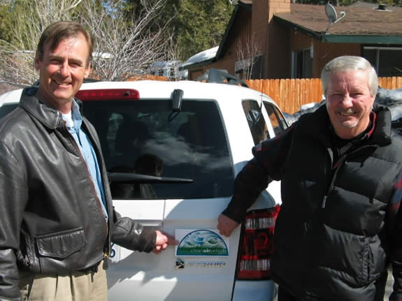 "Mayor Herrick and Mayor Pro Tem Jahn place a ""clean air"" decal on one of the City's hybrid vehicles."
