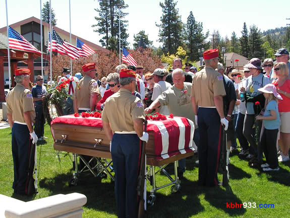 The well-attended ceremony allowed attendees to place a red carnation (as offered by the Girl Scouts) atop the symbolic casket, which had been in the Village procession.