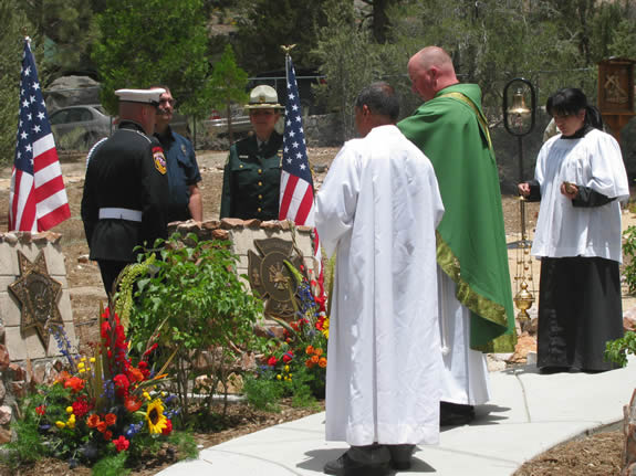 The June 28 ceremony concluded with a blessing by Father Mike (in green). The memorial walkway is at St Joseph's, which is on the North Shore just east of Stanfield Cutoff.