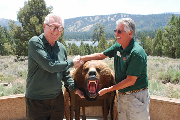 Fred Tshoop donates the grizzly bear, which has been in his family for over a century, to Denis Thomas for use by the Big Bear Discovery Center.
