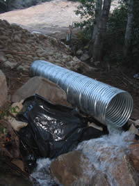 A diversionary pipe is in place during construction, to mitigate further erosion.