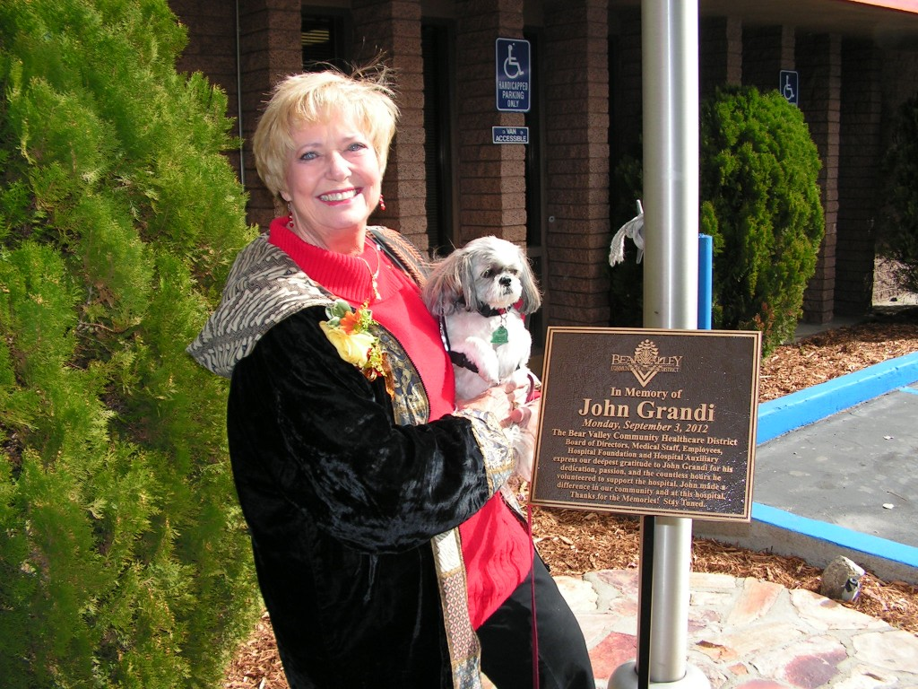 Julie Grandi with Holly at the flag pole plaque dedication to John Grandi at Bear Valley Community Hospital.
